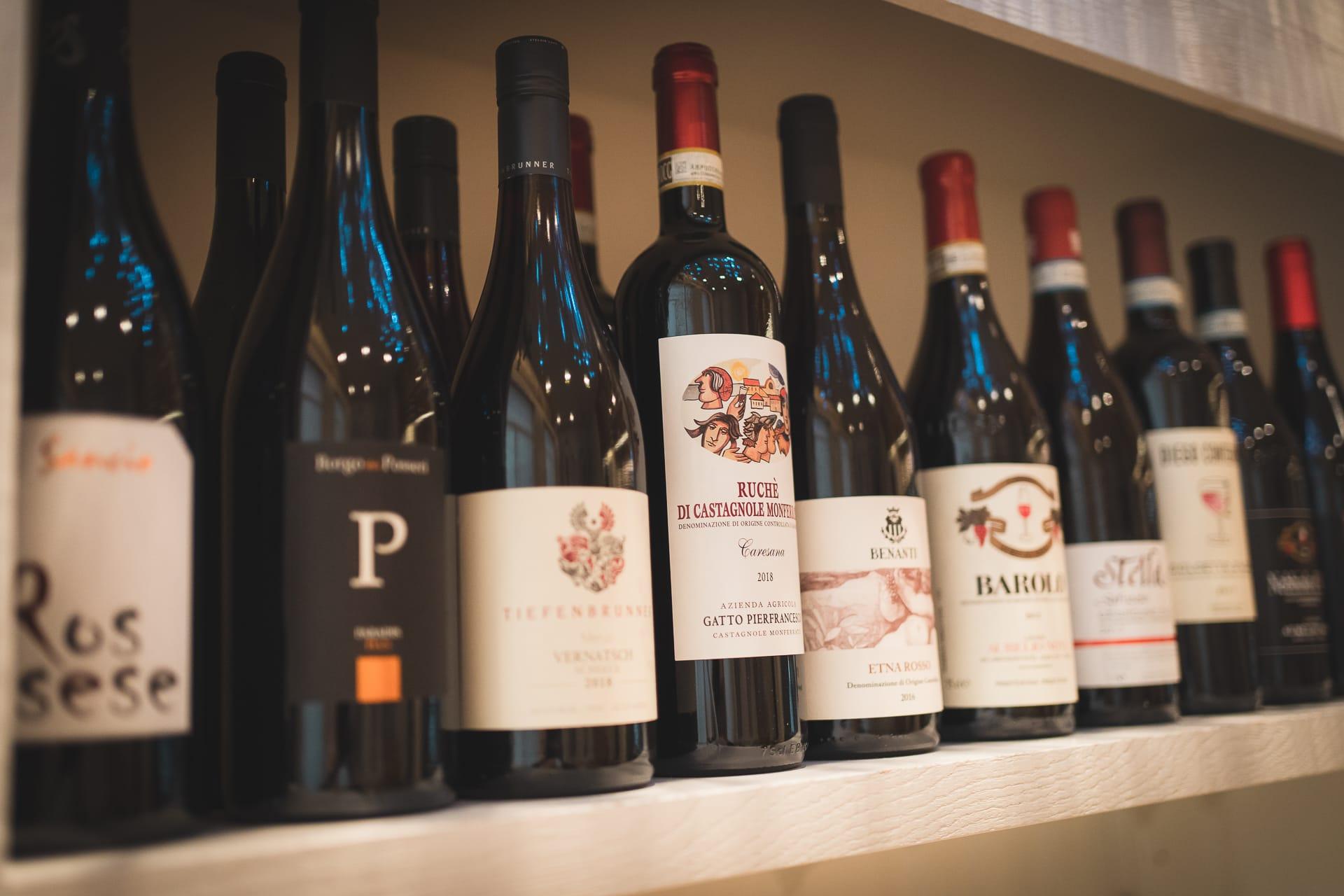 Bottiglie di vino rosso pregiato su scaffale in vista laterale