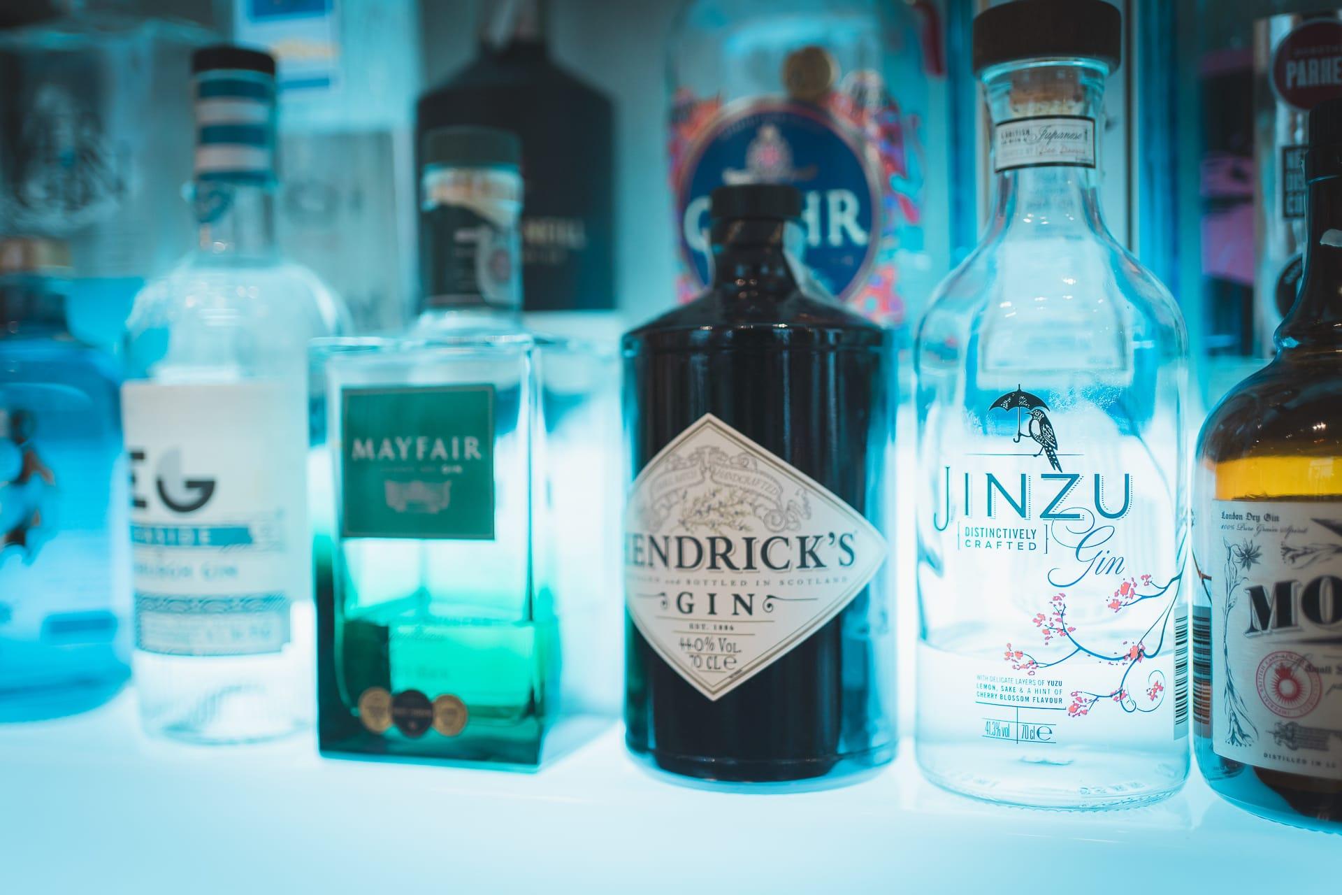 Bottiglie di gin pregiati su scaffale illuminato con luce azzurra