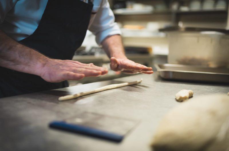 mani del cuoco che preparano grissini artigianali in cucina