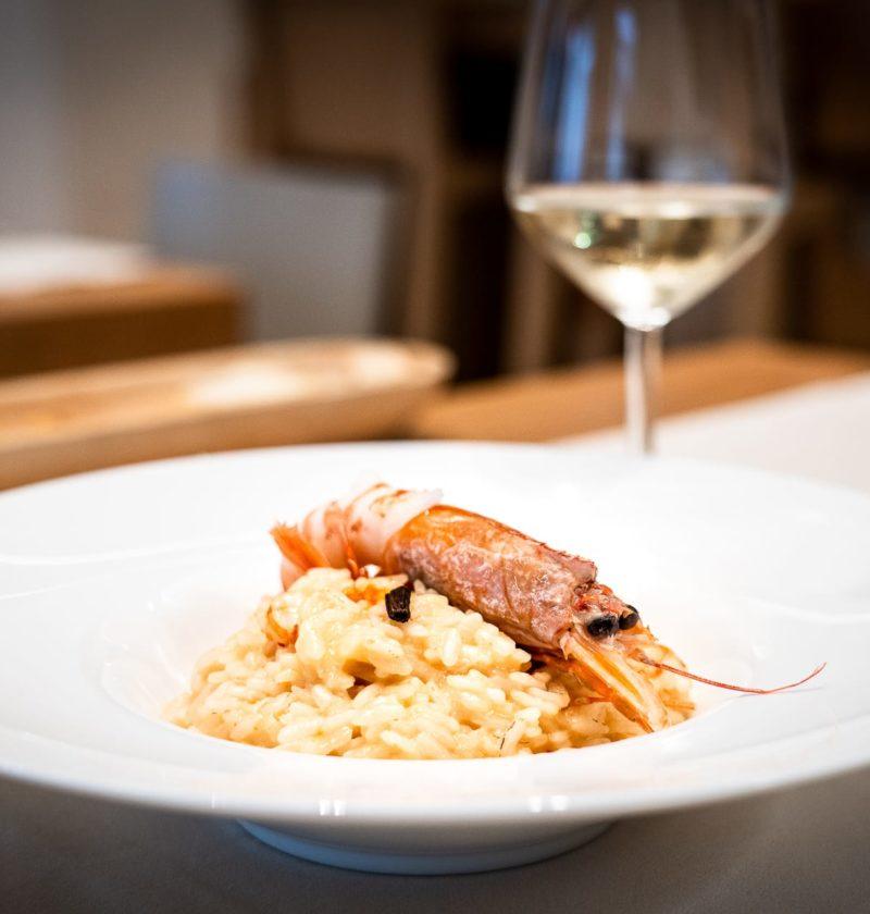piatto di riso agli scampi e bicchiere di vino bianco