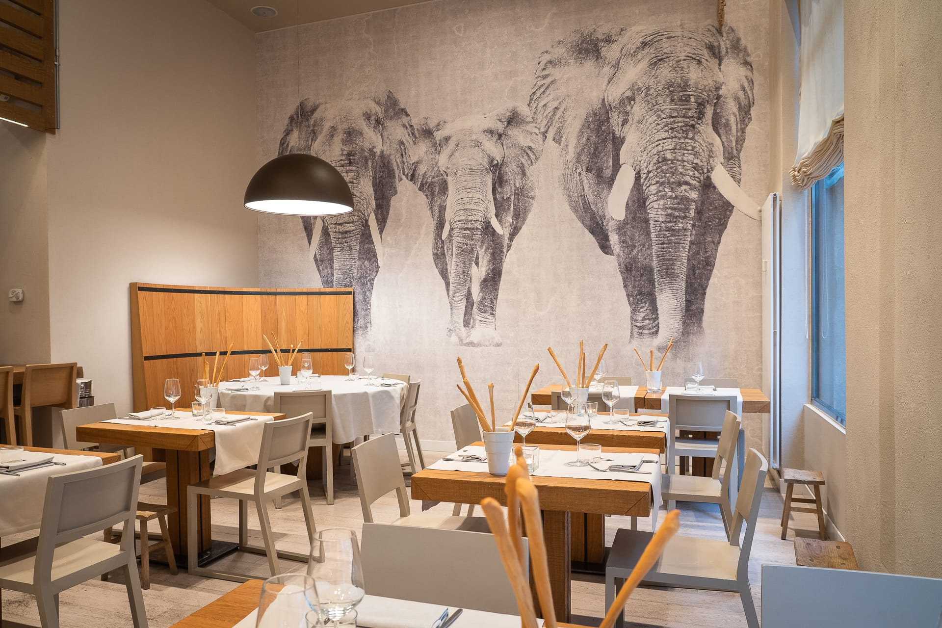 sala principale ristorante angolo 16 con tavoli apparecchiati e murales di elefanti