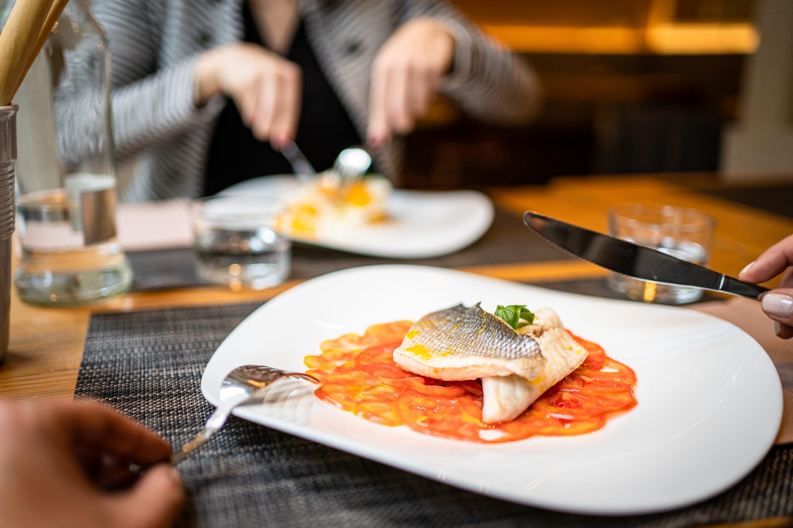 persone che mangiano piatto di pesce a tavola